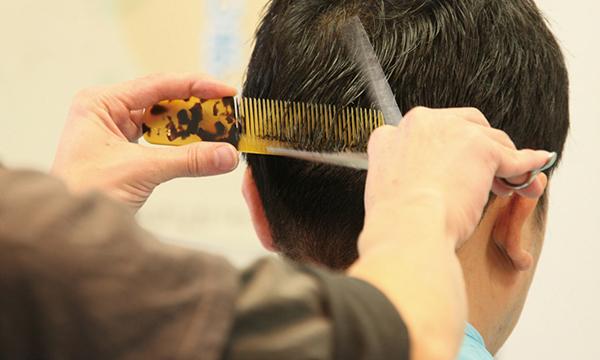 美容室でスタイリストに髪をカットしてもらっている様子